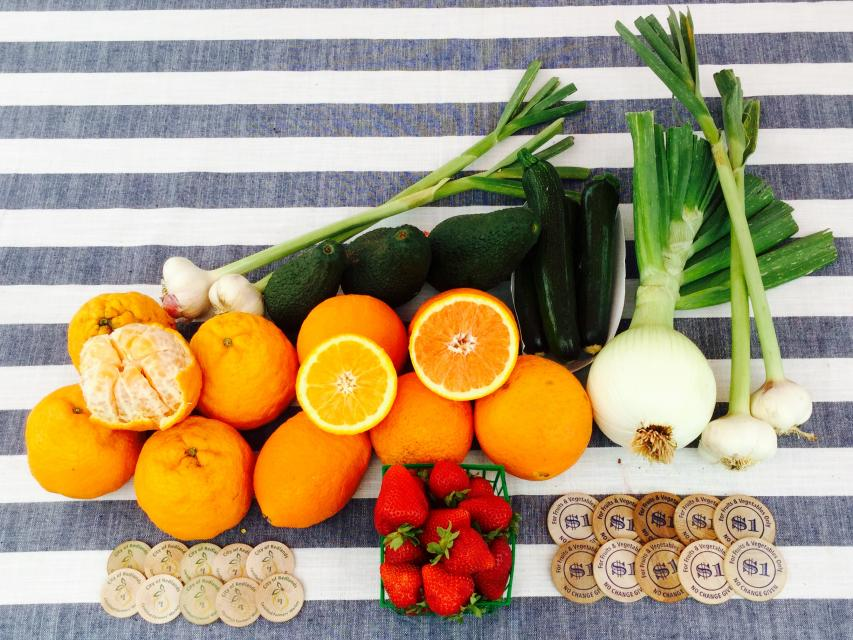 oranges strawberries onions and market match coins on striped tablecloth