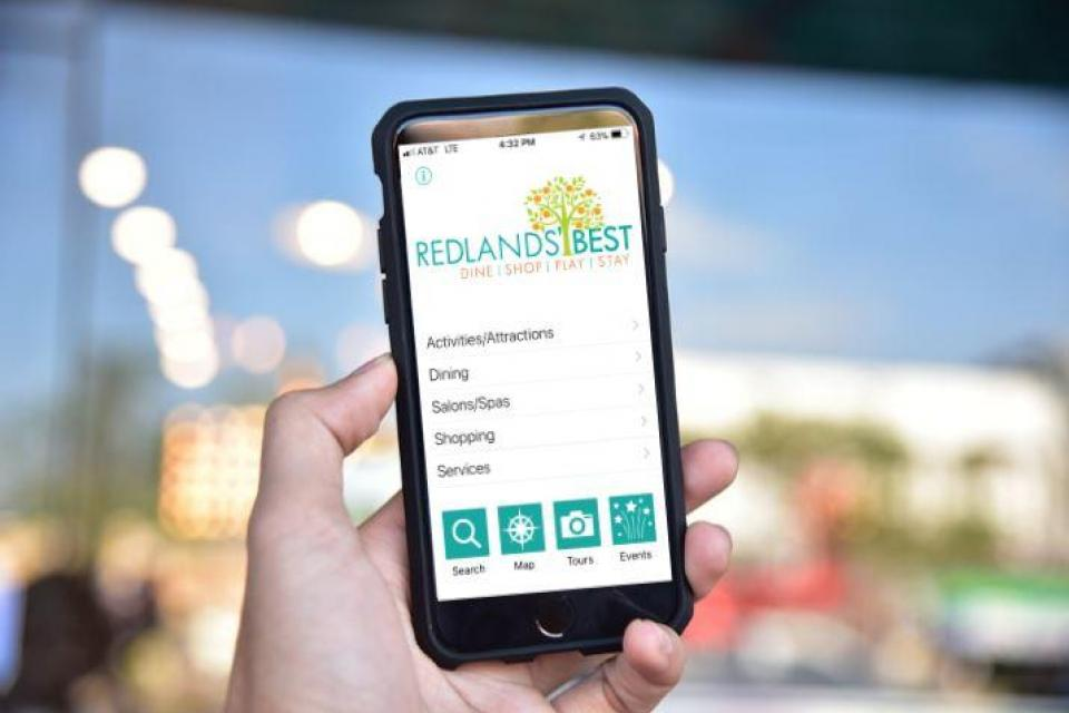 Photo of person holding a mobile phone displaying the Discover Redlands mobile app.
