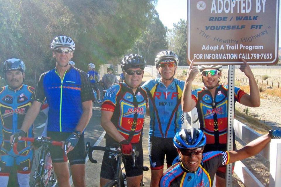Bike Riders with Adopt a Trail Sign