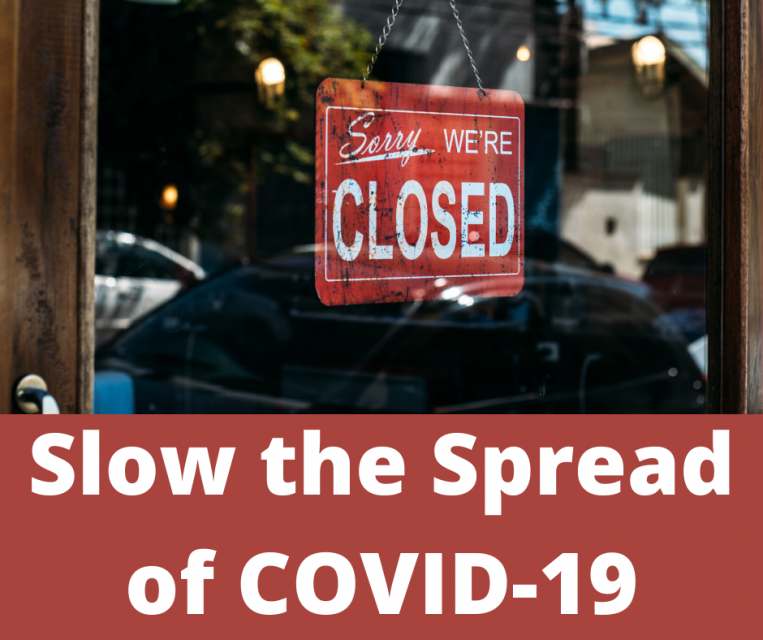 "Sign in a shop window that reads, ""Sorry, we're closed"" and text saying, ""Slow the Spread of Covid-19"""